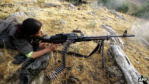 A female member of the PKK practises firing her rifle