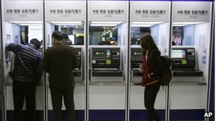 Depositors try to use automated teller machines of Shinhan Bank while the bank's computer networks are paralyzed at a subway station in Seoul, South Korea, Wednesday, March 20, 2013.
