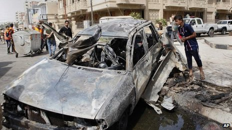 A boy inspects a car destroyed by a bomb blast near the Green Zone in Baghdad (19 March 2013)