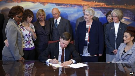 Sponsors and family members of victims watch as Colorado Governor John Hickenlooper signs the bills into law in Denver on on 20 March 2013.