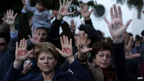 "Cypriots show their palms reading ""No"" during a protest against an EU bailout deal"