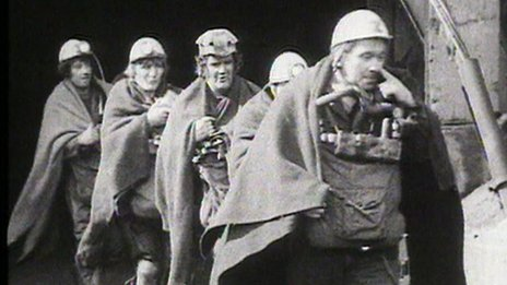 Men wearing hard hats walking out of a mine