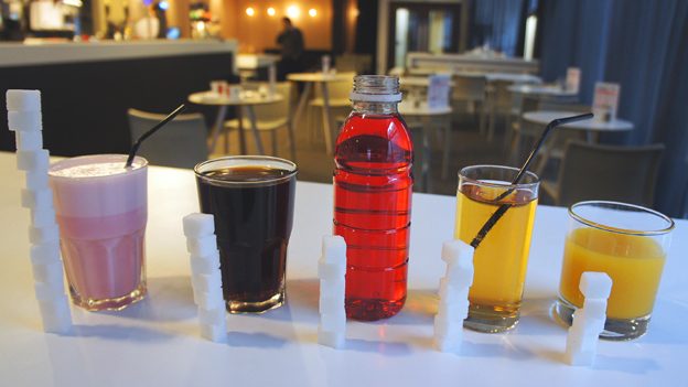 Popular soft drinks lined up with the amount of sugar they contain stacked next to them in sugar cubes