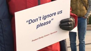 """A Derby carer holding a sign which reads """"Don't ignore us please"""""""