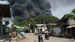 Black smoke rises from burning buildings as residents ride motorcycles in a street in riot-hit Meiktila, central Burma, on 21 March 2013