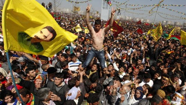 Demonstrators hold flags and portraits of jailed PKK leader Abdullah Ocalan during a gathering to celebrate New Year in Diyarbakir