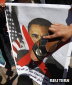 protester waves shoe in front of Obama poster