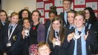 Dallam School students stand with their School Report passes with Jennie Dennet of BBC Radio Cumbria