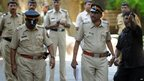 Indian police officials gather outside the house of Bollywood star Sanjay Dutt in Mumbai