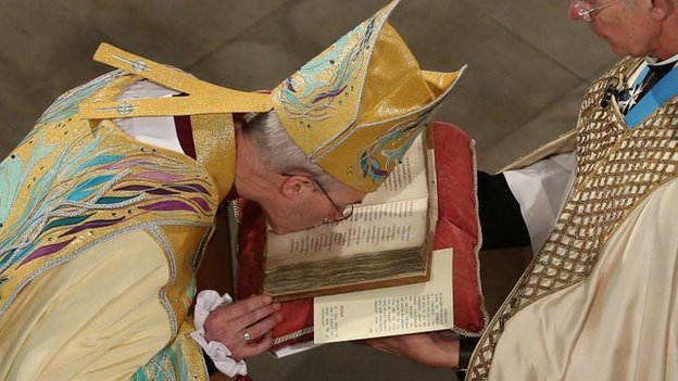 Archbishop Justin Welby kisses the book