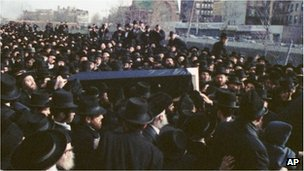 Thousands of mourners carry the coffin of Rabbi Haskel Werzberger in New York, 1990