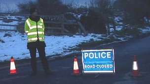 Road closed sign and police officer near accident