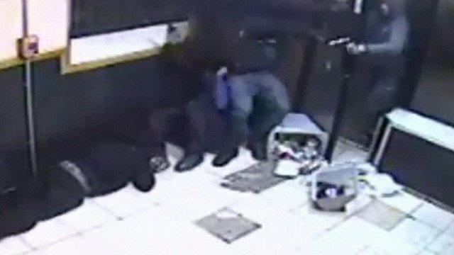 Gunman (far right) tries to shoot as several men try to keep the door closed