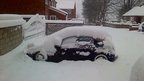 A car covered in thick snow. It's parked in a residential street, in front of a driveway gate which is also covered in snow.