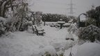 A snow covered garden and bench.