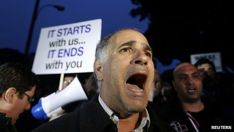 A protester shouts slogans during a rally by employees of Cyprus Popular Bank outside the parliament in Nicosia March 21, 2013