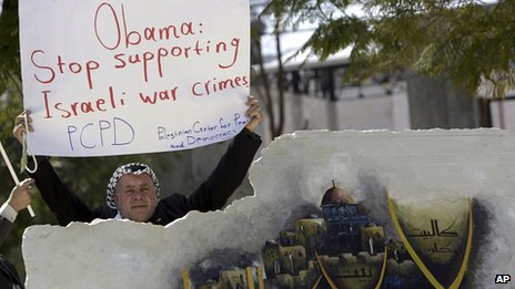 Palestinian man holds banner urging US to stop supporting Israel during protest against Mr Obama's visit.