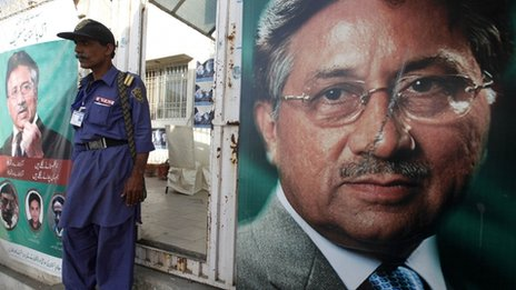 "A security man stands guard at the entrance of former president Pervez Musharraf""s campaign office, decorated with posters in Karachi"
