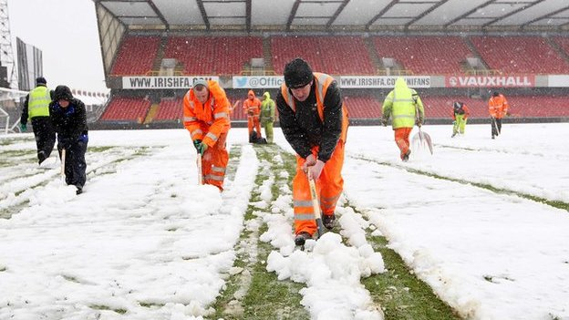 Snow being cleared off a football pitch