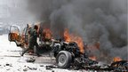 A policeman runs through burning vehicles in  Mogadishu, Somalia, on 18 March 2013