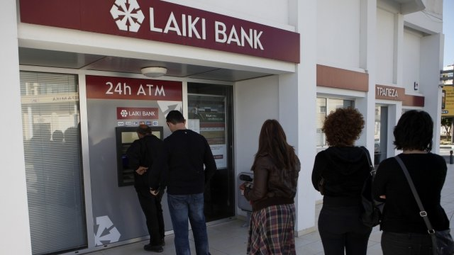 People queue to use an ATM machine outside of a Laiki Bank branch in Larnaca, Cyprus
