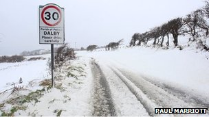 A road sign covered in snow in the Isle of Man