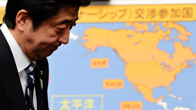 Japanese Prime Minister Shinzo Abe walks before the map of the Trans-Pacific Partnership  participating countries