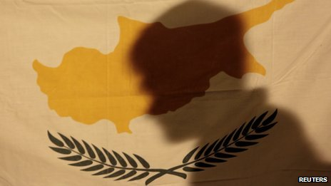 Protester casts a shadow onto a Cypriot flag in Nicosia on 24/3/13