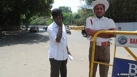 Man on phone next to cardboard traffic officer