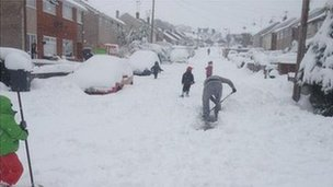 People clearing snow in Mynydd Isa
