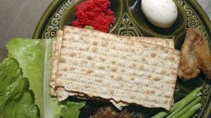 Image of a seder plate containing unleavened bread, egg, lamb shank bone and lettuce