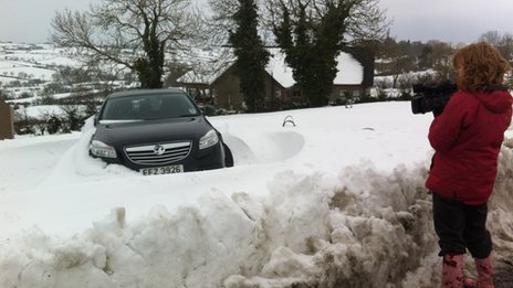 Reporter films car in snow drift