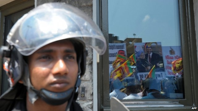 Pro-government activists are reflected in the glass of the US embassy during a protest in Colombo