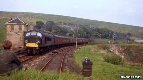 At lonely Riccarton Junction in a late afternoon of spring 1966, 'Peak' Type 4 class battles up the 1 in 75 towards Whitrope Summit with the daily service conveying through coaches from St Pancras. Latterly the only passenger services which did not call at Riccarton – which depended on trains for its public transport – were this daytime London train, its southbound equivalent, the night trains in each direction and the seasonal service between Dundee and Blackpool North. The first signs of growth of the Forestry Commission plantations around Riccarton can be seen in the background; sadly – and perhaps crucially – despite inconsistent efforts by BR, no timber moved on the Waverley Route in the 1960s.