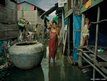 A pregnant woman washes in an open sewer in Andong