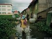 Here a woman picks water snails for food in an Andong