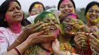 "Indian women smear colors on each others faces as they celebrate ""Holi"", the Indian festival of colors in Allahabad, India,"