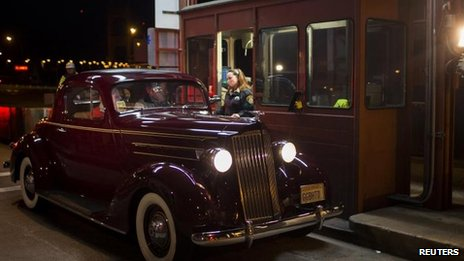 Collector Marilyn Alvardo receives the last toll from Jim Eddie in his vintage 1937 Packard, 26 March