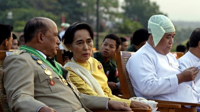 Opposition leader Aung San Suu Kyi, in yellow, talks with Deputy Border Affairs Minister Maj. Gen. Zaw Win, left, during Myanmar's 68th anniversary celebrations of Armed Forces Day, in Naypyidaw, Myanmar, Wednesday, March 27, 2013.