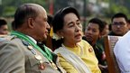Burmese opposition leader Aung San Suu Kyi (R) speaks with Deputy Minister for Border Affairs Major General Zaw Win (L) during the 68th Armed Forces Day in Naypyitaw, 27 March