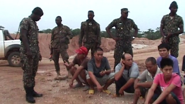 Ghanaian officials surrounding suspects