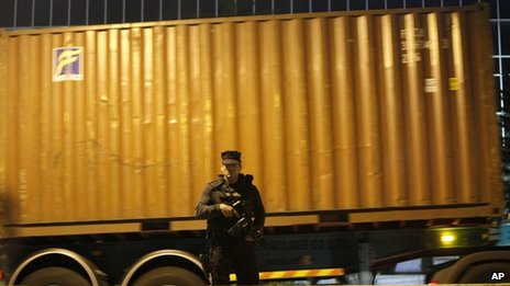 An armed police officer guards several container lorries arriving at the country's Central Bank in Nicosia, Cyprus, on Wednesday