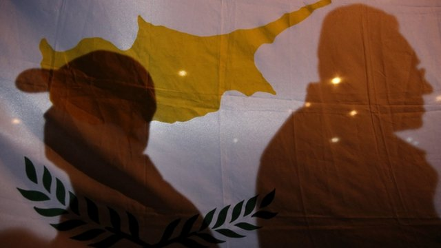 Protesters cast their shadows on a Cypriot flag during an anti-bailout rally outside the presidential palace in Nicosia