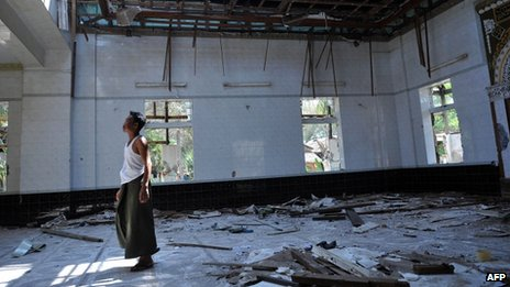 A man walks in a mosque destroyed after communal violence in central Burma (28 March 2013)