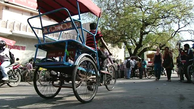 A tricycle taxi looks for tourist passengers
