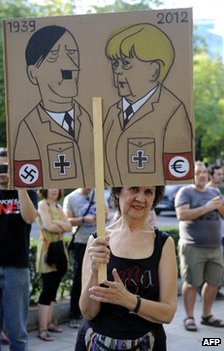 A protester in Madrid holds a placard likening German Chancellor Angela Merkel to Hitler, 6 September 2012