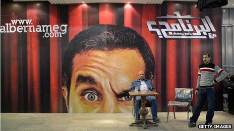 Egyptians gather in front of a poster of Egyptian satirist Bassem Youssef at a theatre in Cairo on January 22, 2013