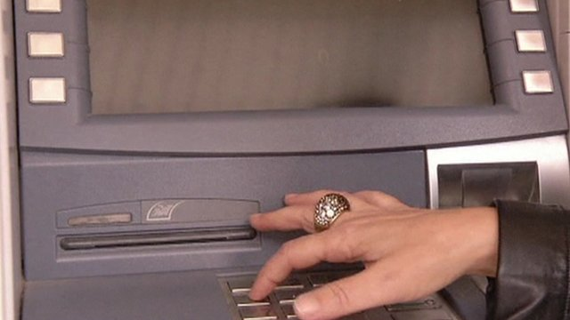 Woman's hand typing in numbers at cash machine