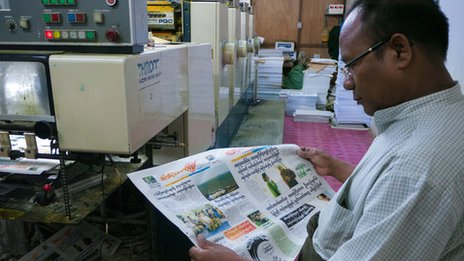 Printer and publisher U Win Htay looks at the front page of his new daily, Standard Time, one of the first four private daily newspapers to be produced in Burma for half a century