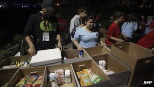 Volunteers sort boxes of dry food provided by concert-goers